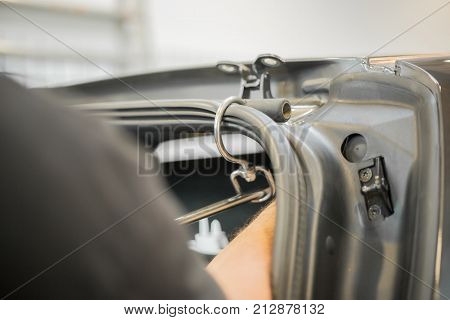 Professional is repairing dents in a car