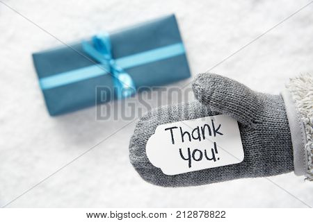 Glove With Label With English Text Thank You. Turquoise Gift Or Present On Snow In Background. Seasonal Greeting Card.