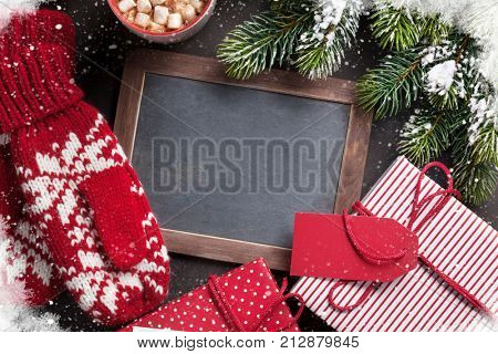 Christmas fir tree, gift, mittens and chalkboard for your greetings. Top view with copyspace