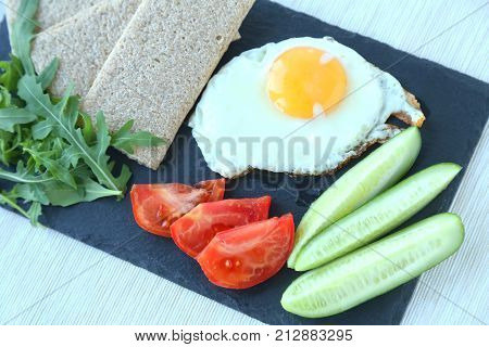Fried egg  with cucumbers, fresh tomatoes and aragula. Healthy breakfast