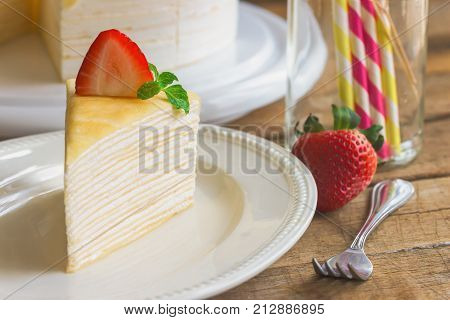 Delicious crepe cake on white plate decorated with mint served with strawberry sauce on wood table so soft sweet and sour. Homemade bakery concept of crepe cake french dessert for birthday cake or cafe. Strawberry crepe cake ready to served.