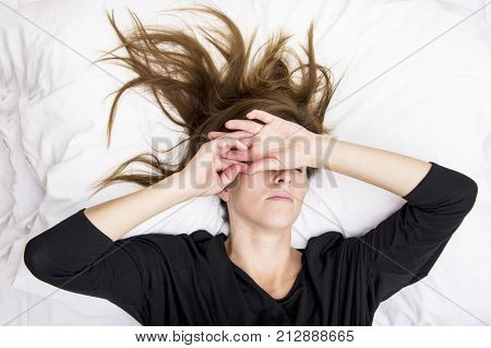 Depressed young woman is lying in her bed, covering her eyes.Sorrow concept.