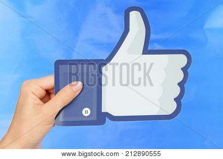 Kiev Ukraine - September 4 2017: Hand holds Facebook logo printed on paper on blue paper background. Facebook is a well-known social networking service