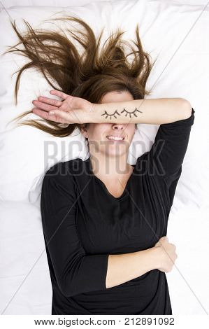 young woman is lying in her bed, joking. She is replacing her eyes by covering it with her painted arms. Lifestyle concept. poster