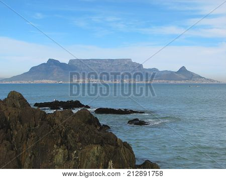 VIEW FROM BLOUBERG STRAND, CAPE TOWN, SOUTH AFRICA, WITH HUGE BOULDERS IN THE FORE GROUND AND TABLE MOUNTAIN IN THE BACK GROUND 42zx