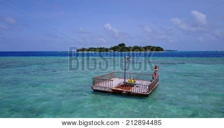 young beautiful girl sunbathing on pontoon with drone aerial flying view in clear blue sea and sunshine