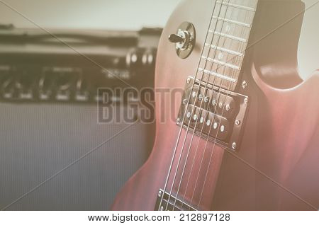 Red electric guitar and classic amplifier on a grey background.