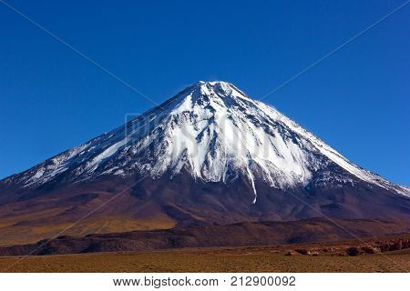 Stratovolcano Licancabur with its characteristic snow peak in Atacama Desert Chile. The volcano is a part of the Andean Volcanic zone with characteristic cone profile.