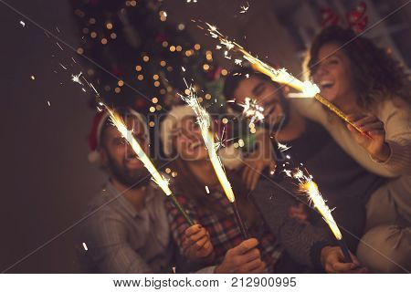 Group of young friends having fun at a New Year's celebration holding sparklers at a midnight countdown. Selective focus on the sparklers