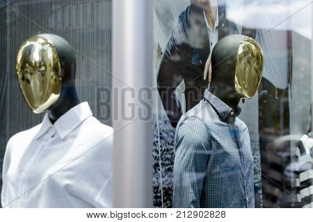 Male and female mannequins with mirror faces in the shop window.
