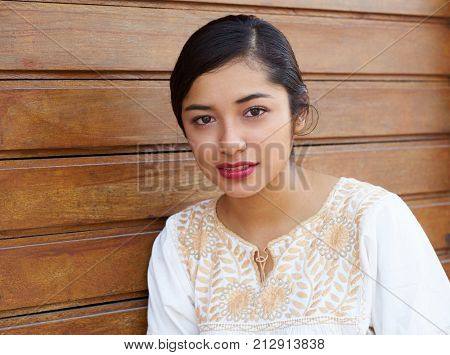 Mexican latin woman with ethnic dress in wooden background