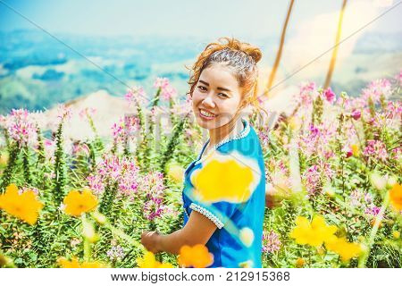Asian women travel sleep relax. women hill tribe in the field of flowers Cosmos sulphureus. Thailand