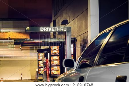 BANGKOK THAILAND - NOVEMBER 04: A white car drives into a Mcdonald's DriveThru in the evening in Bangkok on November 04 2017.