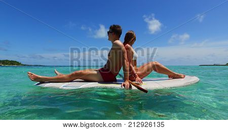 two 2 people romantic young people couple paddleboard surfboard with drone aerial flying view on a tropical island of white sand beach and blue sky and sea.