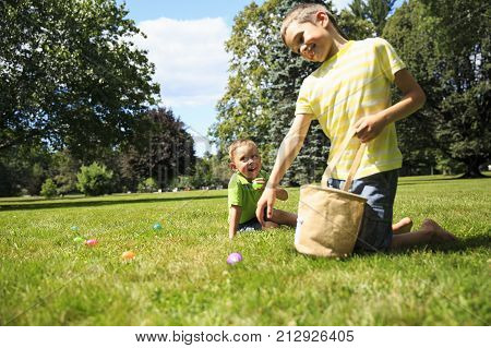 children having fun collecting Easter eggs. cheerful boys pick up colorful eggs from the grass during the Easter eggs hunt. Copy space for your text