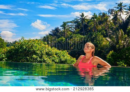 Beautiful tanned woman on summer beach holiday relaxing in luxury spa hotel in infinity swimming pool with tropical jungle view. Healthy lifestyle family travel background. Bali island tour.