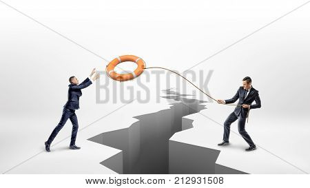 A businessman throws a lifeline with an orange life buoy over a large earthquake crack to another businessman. Business and cooperation. Help your colleagues. Workplace assistance.