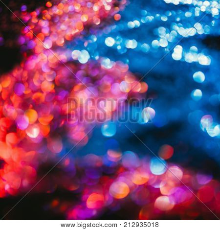 Multicolor abstract glitter background. Defocused blur bokeh flares. Fire and water elements concept