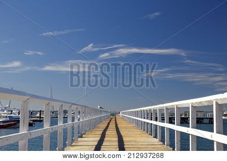 Perspective view of a wooden pier on the ocean. Vintage wooden pier at the beach