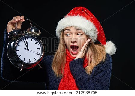 Surprised girl wearing Santa hat holding big alarm clock time approaching midnight with mouth opened in expression, looking at clock, over dark background