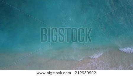waves water texture breaking and crashing with drone aerial flying view of aqua blue and green clear sea ocean