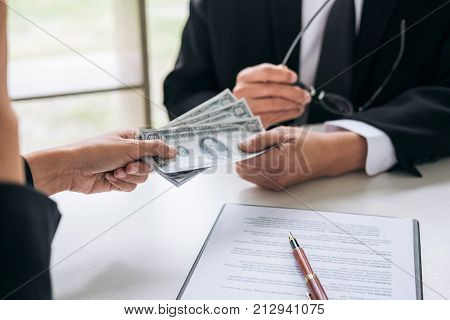 Bribery and corruption concept bribe in the form of dollar bills Businessman giving money while making deal to agreement a real estate contract and financial corporate.