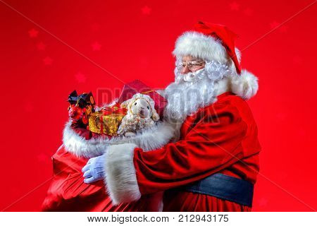 Christmas and New Year concept. Portrait of good old Santa Claus holding a sack with gifts and toys. Red background.