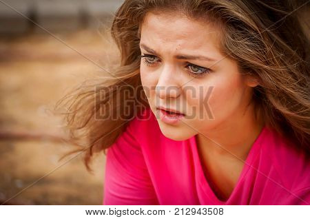 Young and attractive Caucasian girl with long straight hair talking to someone.