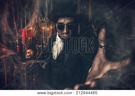 Halloween. Scary frightening man in black holds out his hand. Old abandoned castle. The Dark Lord. Vampire man.