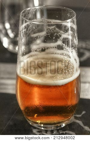 Close up of a frothy glass of beer with condensation