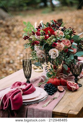 Rustic wedding decoration for festive table with beautiful flower composition. Autumn wedding. Wedding area. Outdoors. Artwork
