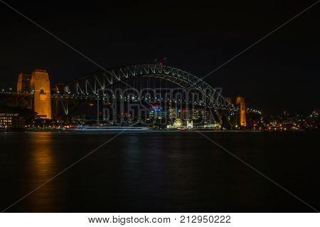 Sydney Australia - March 24 2017: Black cloudy night photo of lighted Luna Amusement Park visible under slightly lighted Harbour Bridge.