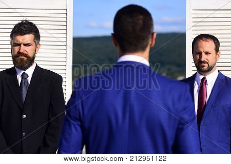 Businessmen Wear Smart Suits And Ties On Wooden Wall