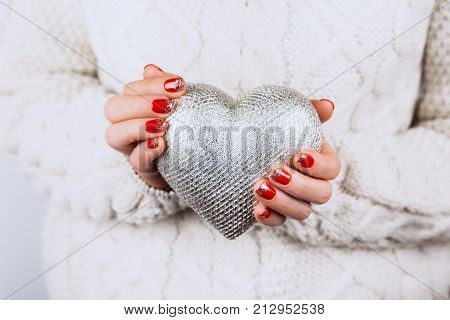 Woman's hands with beautiful accurate manicure carefully keep silver heart
