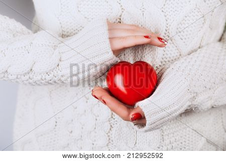 Woman's hands with beautiful accurate manicure carefully keep red heart. White cozy knitted sweater as a backdrop. Concept of giving help to them, who needs.