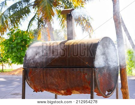 Aged rusted iron barrel barbecue in Mexico Riviera Maya