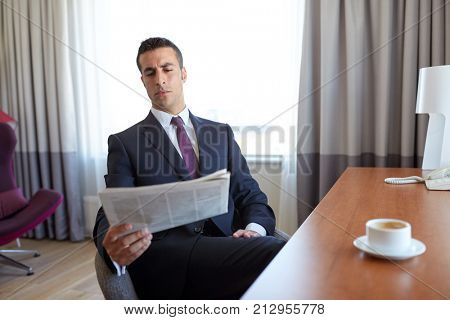 business trip, people and mass media concept - businessman reading newspaper at hotel room