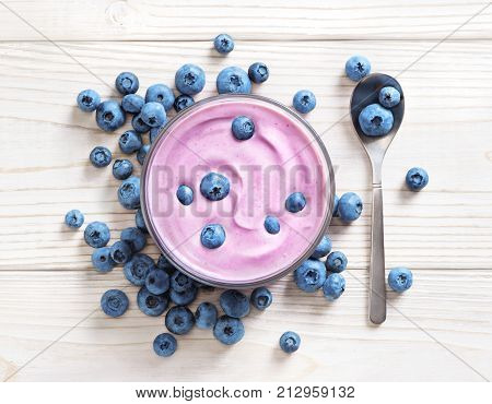 Blueberry yogurt on white wooden table. Fresh yogurt. Healthy food concept. High resolution product. Top view