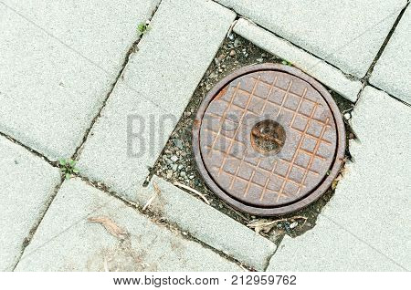 Rusty manhole cover of access point for a shut off valve to a water main along a sidewalk