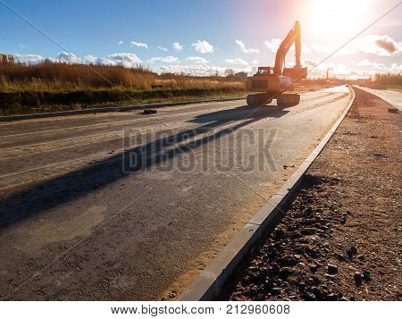 Crawler excavator with bucket rides on construction of high-speed ring road. Heavy machine equipment for excavation works at civil industrial construction. Saint-Petersburg Russia