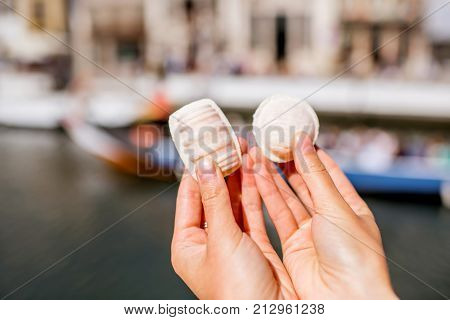 Holding portuguese delicacy called Ovos Moles made of egg yolks and sugar on the water channal background in Aveiro city, Portugal