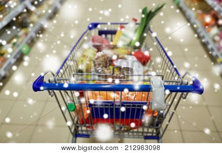 consumerism concept - food in shopping cart or trolley at supermarket over snow