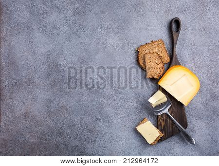 Delicious dutch gouda cheese with cheese slices, multigrain bread and special knife on old wooden board. Healthy food concept with copy space.