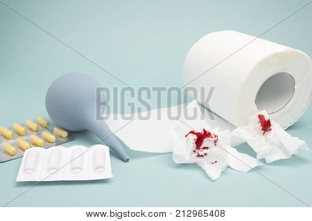 A photo of clyster, enema, yellow pills, used bloody toilet paper and a tiolet paper roll. Hemorrhoids, constipation treatment health problems. Menstrual, hemorrhoids bleeding. Blood drops and traces