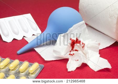 A photo of clyster, enema, yellow pills, used bloody toilet paper and a toilet paper roll. Hemorrhoids, constipation treatment health problems. Menstrual, hemorrhoids bleeding. Blood drops and traces