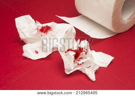 A photo of used shits of bloody toilet paper and a toilet paper roll on the red background. Menstrual, hemorrhoids bleeding. Blood drops, traces. Hemorrhoids, constipation treatment health problems