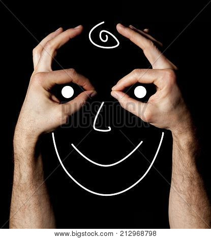 Face with hands happiness facial expression on black background. A human face made with hands. Facial expression happy mood. Concept of happiness to be built with their own hands.