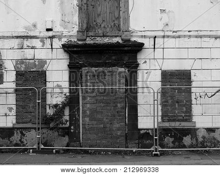 derelict abandoned house on the street awaiting demolition with barriers in wakefield yorkshire englend