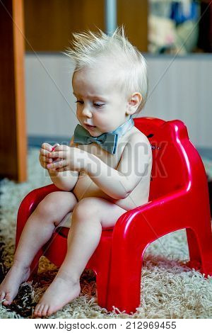 Baby girl sitting on green potty in home interior