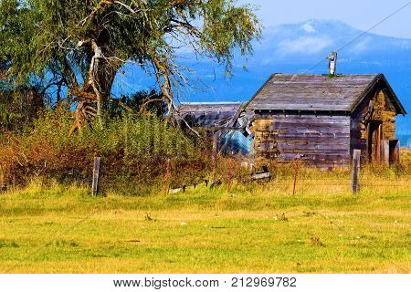 Forgotten abandoned ranchland including a dilapidated wooden cabin taken in the Central Oregon Plains with mountains beyond